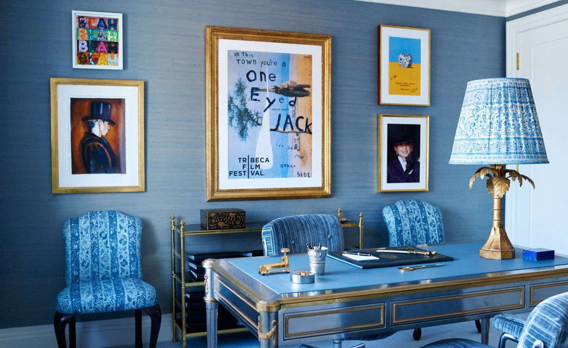 office with blue wall covering, blue upholstered chairs and blue lampshade and gallery of frames behind