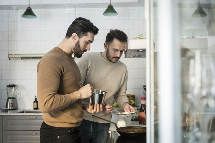 Gay couple preparing food in kitchen at home