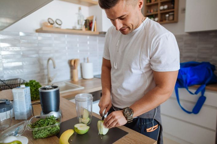 young man is making smoothie before exercising