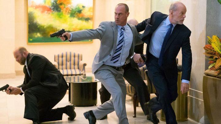 un grupo armado sale de una sala en la película los conspiradores