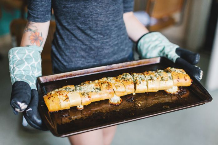 Mid section of young women holding stuffed baguette on baking tin