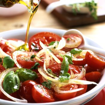 olive oil pouring over tomato and basil salad