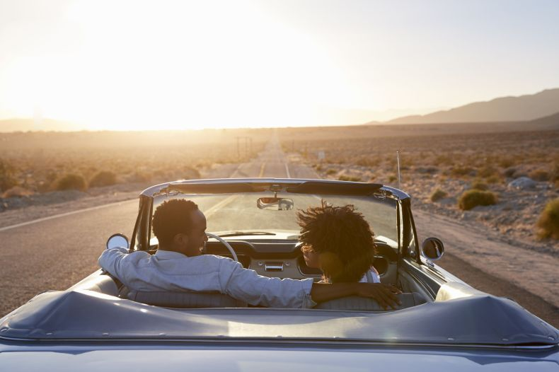 best road trip songs   rear view of couple on road trip driving classic convertible car towards sunset