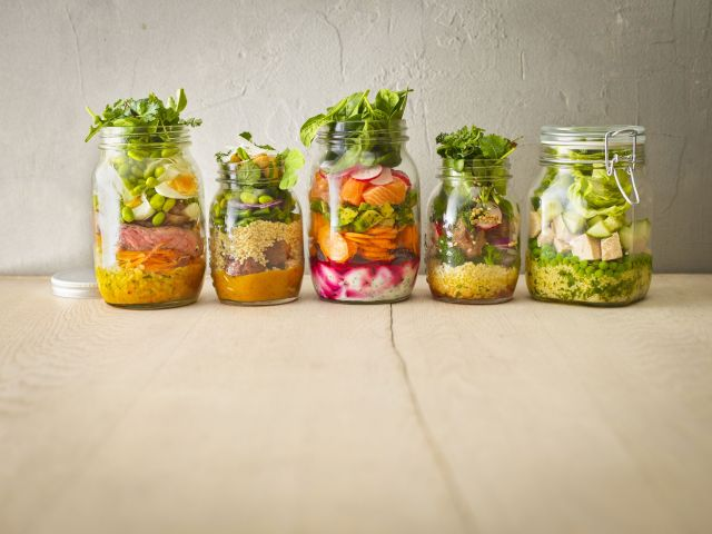 Row of five preserving jars with various salads