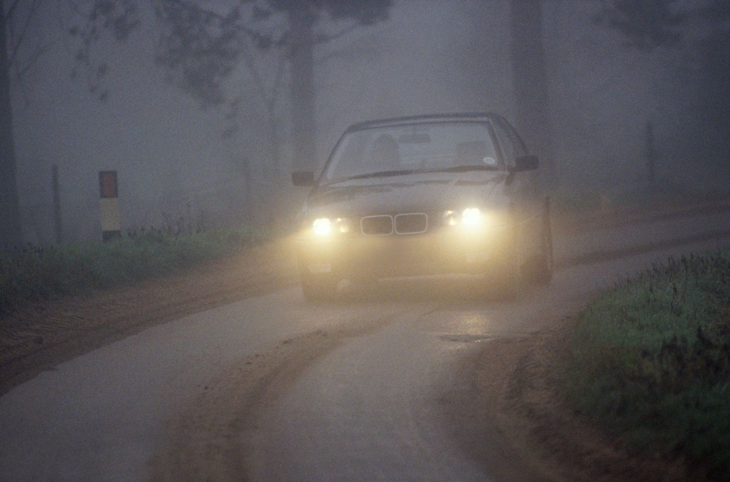bmw 5 series germany driving along country lane in fog, england