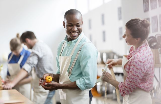 Smiling woman tying apron for man in cooking class kitchen