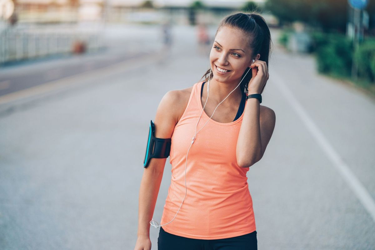 smiling young sportswoman with arm band and royalty free image 997350994