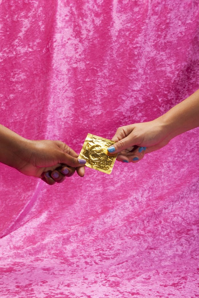 Two Young Women Holding Condom