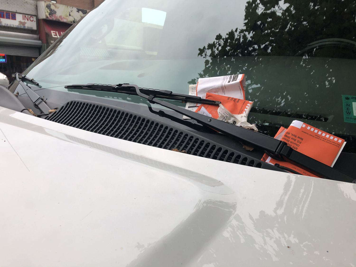 suv with several parking tickets in windshield wipers