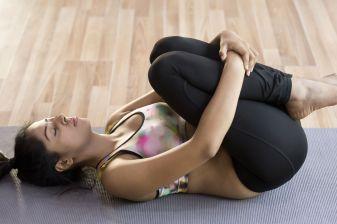 Young woman in apanasana yoga pose