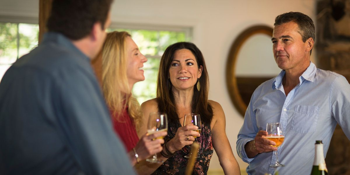 Two mature couples drinking white wine at dinner party