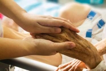 高齢者の手をマッサージする