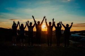 夕陽に歓喜する仲間の後ろ姿