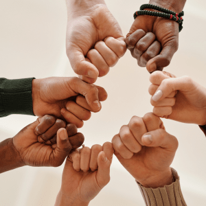 people of different racial backgrounds unite by putting their fists together. This is a represents the meaning of D&I.