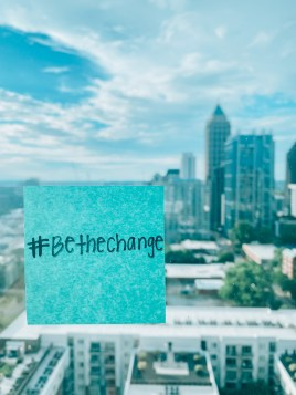 """post-it note reading """"#BeTheChange"""" on window with start-up hub, Atlanta, behind it. It represents the Atlanta-based company, Hire Ventures' summer series initiative """"Be The Change: Diversity & Inclusion in the Workplace"""" which discusses a range of D&I topics include D&I meaning."""