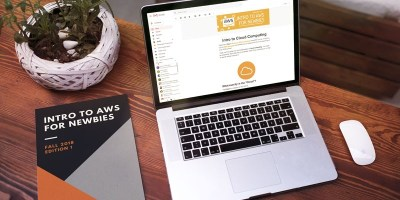 """Intro to AWS for Newbies"" ebook in a physical book form next to a laptop with ""Intro to AWS for Newbies"" newsletter course pulled up on the browser"