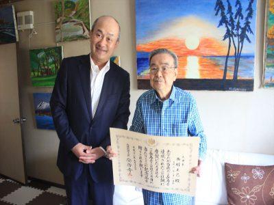 高橋清田区長から100歳の祝状と銀杯を受け取った西村さん(右)