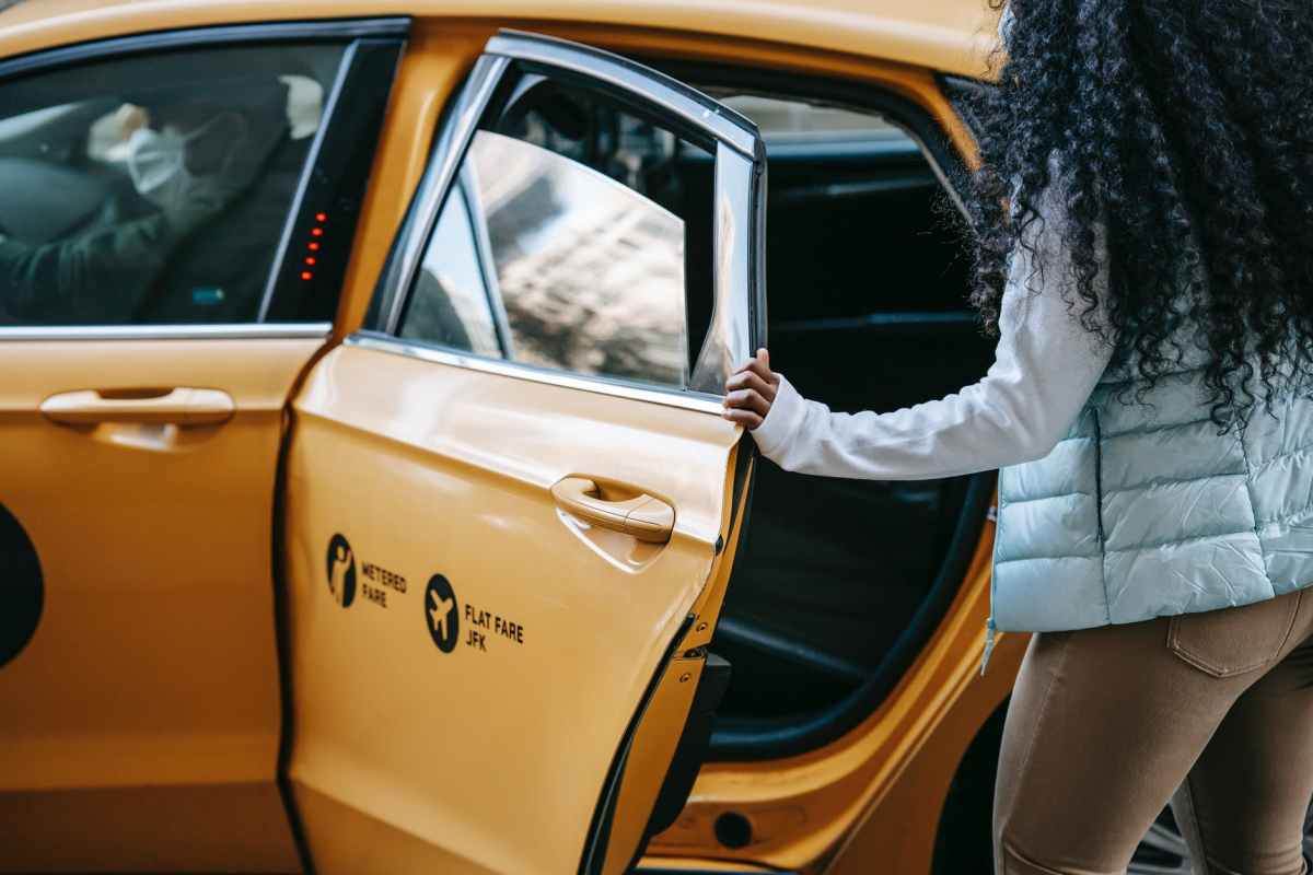 anonymous african american woman getting into cab parked on street