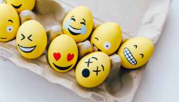 yellow painted eggs with various facial expressions