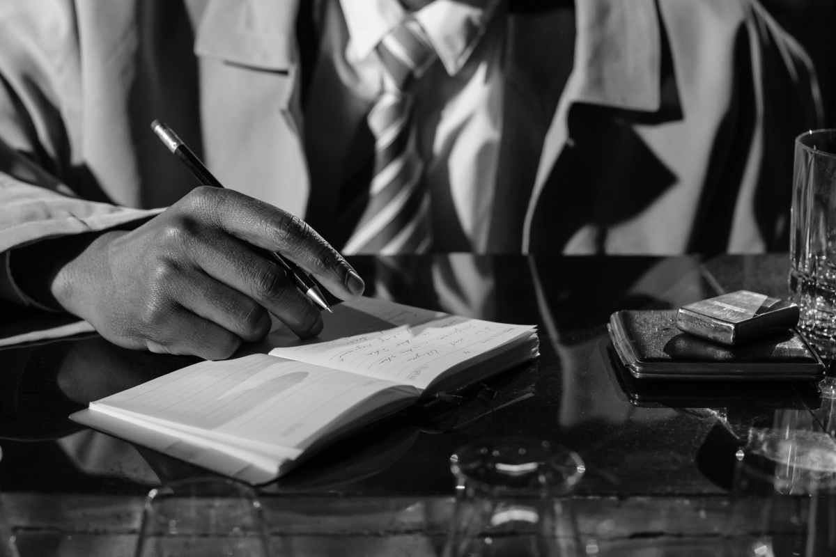 monochrome photo of person taking down notes