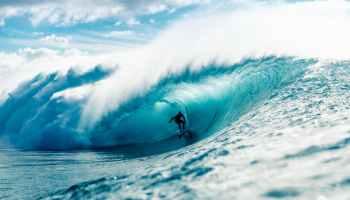 man riding surfboard in wavy ocean