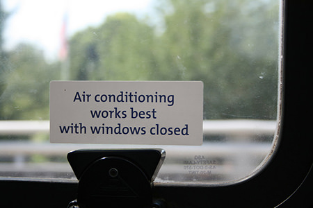 Window with 'Air conditioning works best with windows closed' notice