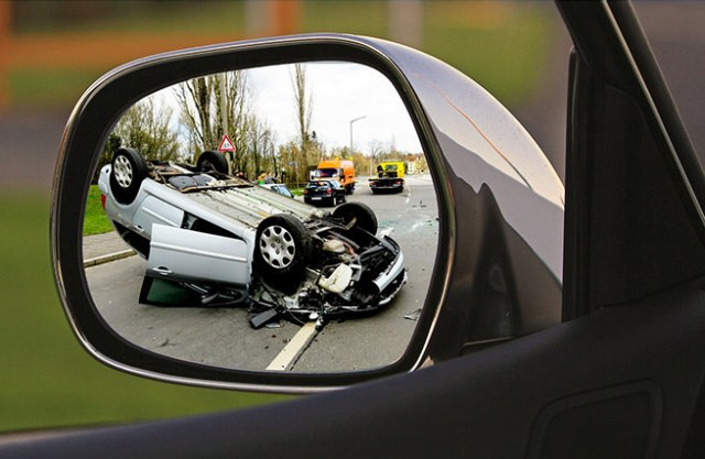 Overturned car seen through a rear view mirror