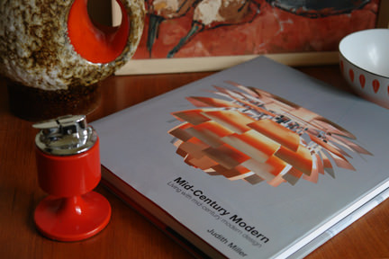 'Mid-Century Modern' by Judith Miller surrounded by vintage Mid-century modern homewares including a West German fat lava vase, bright orange pedestal cigarette lighter, small Cathrineholm enamelware Lotus bowl and still life oil painting