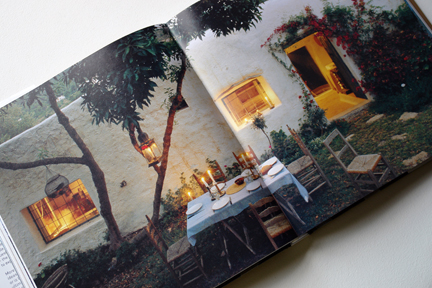 """double page spread showing an antique chairs & set table with lit candles at dusk outside a rustic whitewashed building from """"The Way We Live In the Country"""" by Stafford Cliff & Gilles de Chabaneix"""