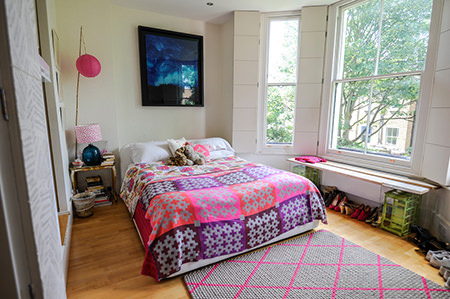 bed covered in pink, purple & grey patterned quilt