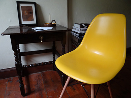 reproduction yellow DSW chair from Metro Furniture with antique furniture