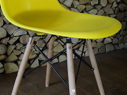 detail of a wooden leg on a reproduction yellow DSW chair from Metro Furniture