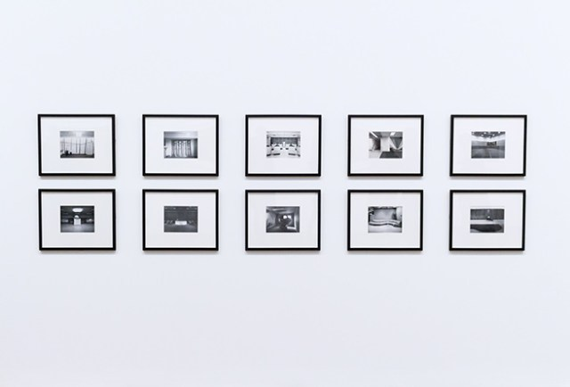two rows of framed black & white artworks
