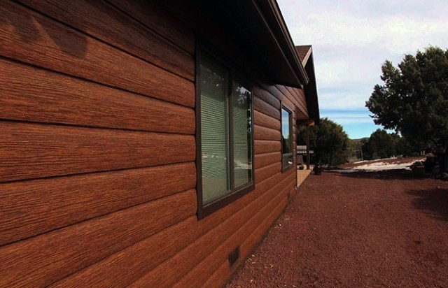 House clad with steel log sidings