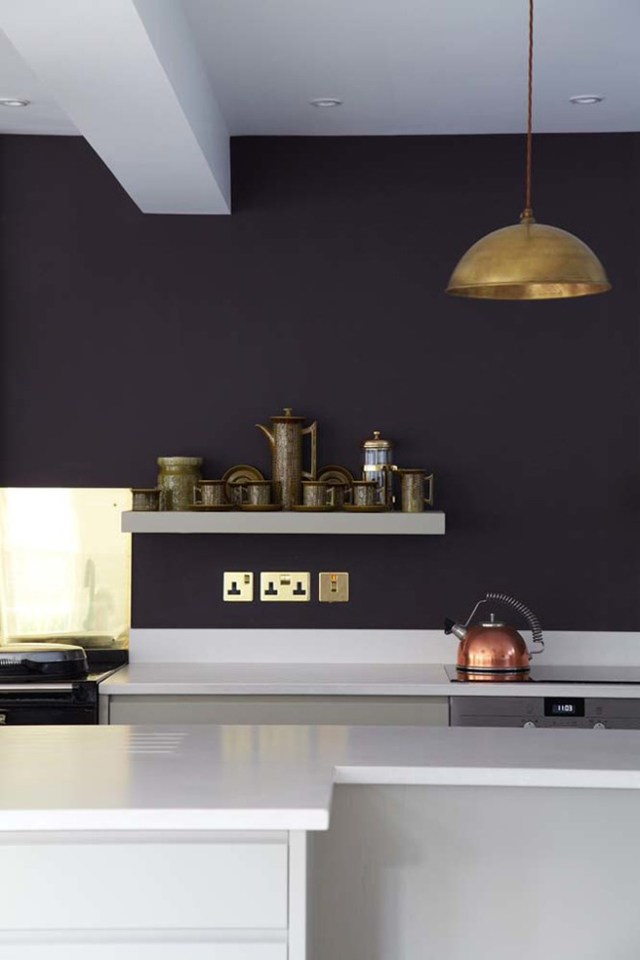 Dark painted kitchen with brass and copper accessories