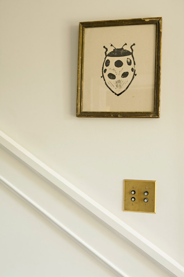 brass light switch finger plate and picture frame on a stairway