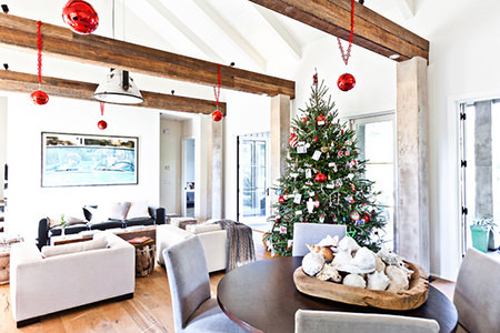 open plan sitting room & dining room with Christmas tree and red baubles hanging from ceiling beams