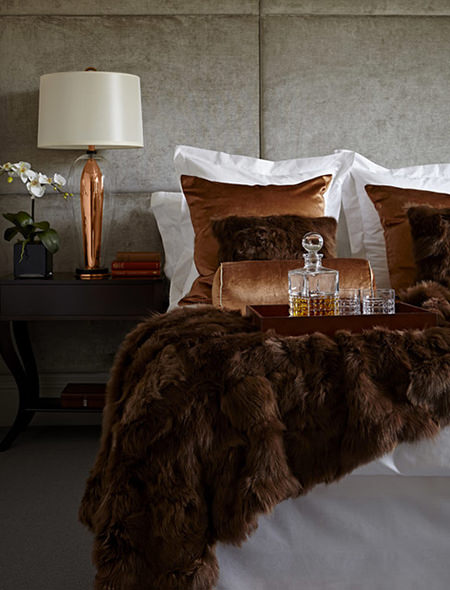 Luxurious bedroom with bedside copper lamp and bed linen