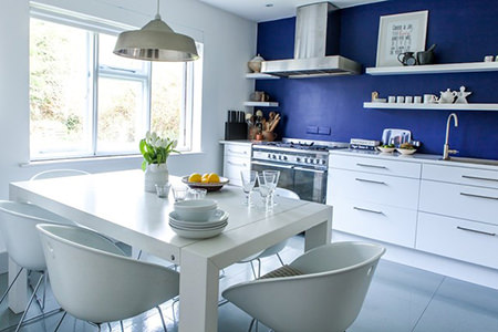 White kitchen with a cornflower blue feature wall