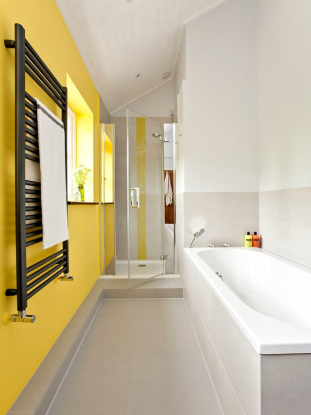 Yellow painted kids' bathroom with yellow tile strip in the shower enclosure