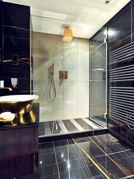 Black tiled shower room with gold shower head, taps and hand basin