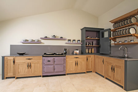 L-shaped kitchen with mauve Aga and floating shelves