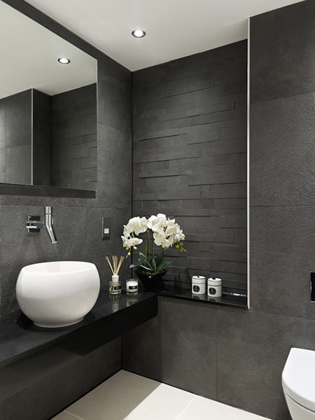 Cloakroom with nearly black painted and tiled walls and splash-back contrasting with white sanitary-ware