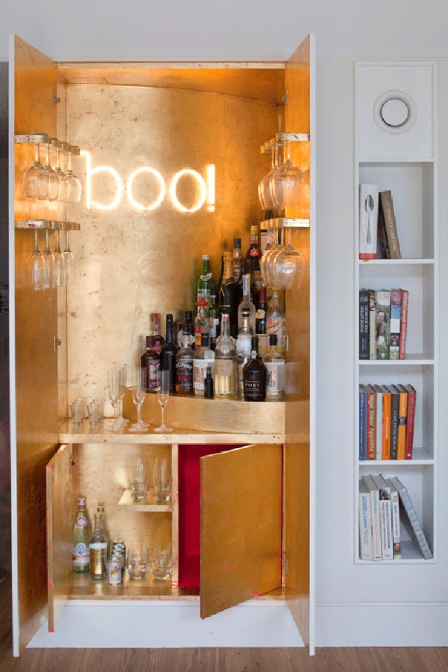 'Boo' neon sign in a gold cabinet cocktail bar