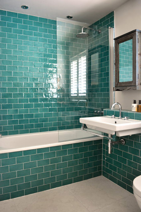 Bathroom tiled from floor to ceiling in turquoise subway tiles