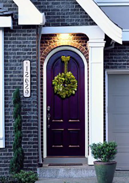 Purple-painted front door with green wreath