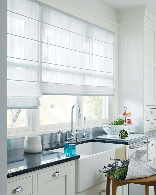 semi-sheer white Roman blinds at a kitchen window