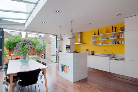 open plan kitchen diner with bright yellow feature wall