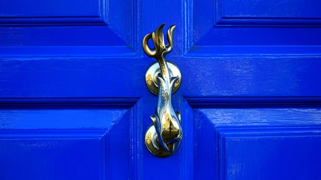 Brass dolphin knocker on a bright blue door