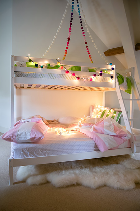 PomPom Galore fairy lights above white-painted bunk beds
